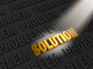 "A spotlight illuminates bright, gold ""SOLUTION"" on a dark background of ""PROBLEM""s"