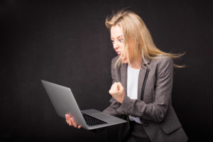 Woman being angry and holding computer