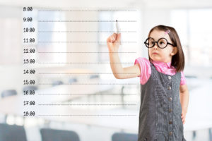 Cute little girl wearing business dress and writing blank appointment schedule. Office background.